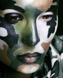 Beautiful young fashion woman with military style clothing and face paint make-up, khaki colored royalty free stock image