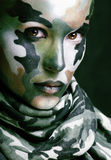 Beautiful young fashion woman with military style clothing and face paint make-up, khaki colored stock photo
