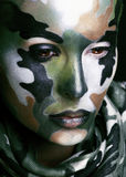 Beautiful young fashion woman with military style clothing and face paint make-up, khaki colored stock photography