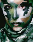 Beautiful young fashion woman with military style clothing and face paint make-up, khaki colors royalty free stock photos