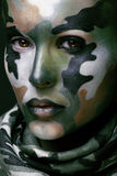 Beautiful young fashion woman with military style clothing and face paint make-up, khaki colors, halloween celebration Stock Photos