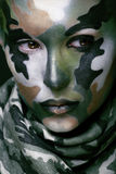 Beautiful young fashion woman with military style clothing and face paint make-up, khaki colors, halloween celebration stock images