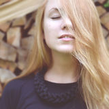 Beautiful young fashion woman posing on firewood wood Stock Images