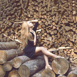 Beautiful young fashion woman posing on firewood wood Stock Photography