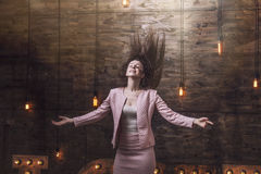 Beautiful young fashion woman in suit with flying hair, arms out stock image
