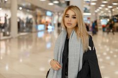 Beautiful young fashionable blond woman with gray eyes in stylish elegant autumn clothes walks through the mall stock photography
