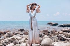 Beautiful Young Fashionable Woman In Elegant Dress Posing At The Stone Beach At Sunset Stock Photo