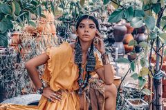 Beautiful young fashionable woman with make up and stylish boho accessories posing on natural tropical background stock image