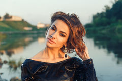Beautiful young fashionable woman posing in dress at the river coast Royalty Free Stock Images