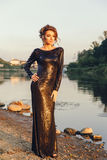 Beautiful young fashionable woman posing in dress at the river coast Royalty Free Stock Image