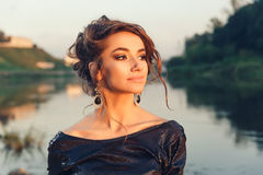 Beautiful young fashionable woman posing in dress at the river coast Royalty Free Stock Photography