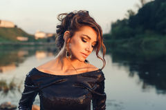 Beautiful young fashionable woman posing in dress at the river coast Stock Images