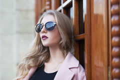 Beautiful young fashionable woman with sunglasses looking aside. Female fashion. Closeup portrait Royalty Free Stock Photography