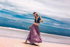 Beautiful young fashionable woman walking by the shore line. Beautiful young fashionable woman walking by the shore stock image