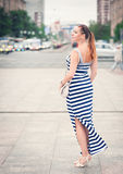 Beautiful young fashionable woman wearing striped dress in the c Royalty Free Stock Photo