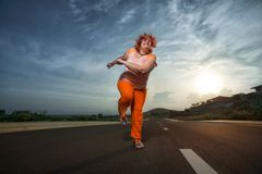 Beautiful young fat woman is runing royalty free stock image