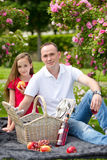 Beautiful young father sitting on a plaid in a green park with her small pretty daughter with a wicker basket for happy picnic Stock Images