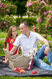 Beautiful young father sitting on a plaid in a green park with her small pretty daughter with a wicker basket for happy picnic Stock Photo