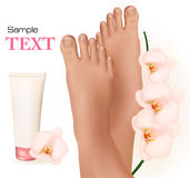 Beautiful young feet with orchids and body cream. Royalty Free Stock Photos