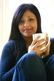 Beautiful young female. Of Asian origin relaxing with a cup of coffee Stock Images