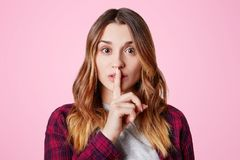 Beautiful young female with appealing appearance keeps fore finger on lips, demonstrates silence sign, asks to be quiet, isolated. Over pink studio background Royalty Free Stock Photography