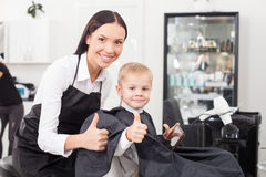 Beautiful young female barber is working in salon Stock Photos