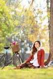 Beautiful young female with bicycle sitting in park Royalty Free Stock Photos