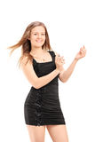 A beautiful young female in black dress spraying a perfume Stock Photography