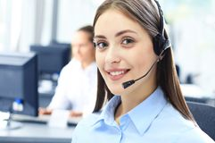 Beautiful young female call center operator with headset in office. Royalty Free Stock Images