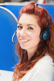 Beautiful young female call center operator with headset in office Stock Photography