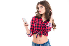 Beautiful young female in checkered shirt using mobile phone Stock Photography