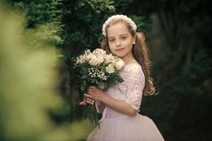 Beautiful young female child wearing wedding dress. In green park royalty free stock photo