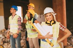 Female Construction Architect. Beautiful young female construction architect at a construction site. She is holding plans and smiling looking at camera Stock Photography