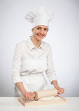 Beautiful young female cook rolling out dough on wooden board. Gray background Royalty Free Stock Image