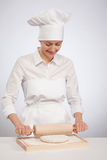 Beautiful young female cook rolling out dough on wooden board. Gray background Royalty Free Stock Photos