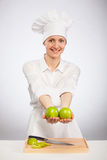 Beautiful young female cook showing an apple Royalty Free Stock Photos