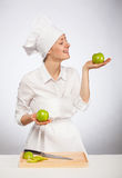Beautiful young female cook showing an apple Royalty Free Stock Image