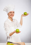 Beautiful young female cook showing an apple Stock Image
