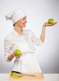 Beautiful young female cook showing an apple Stock Photos
