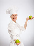 Beautiful young female cook showing an apple Royalty Free Stock Photography
