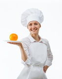 Beautiful young female cook showing orange on a plate Royalty Free Stock Photos