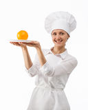Beautiful young female cook showing orange Royalty Free Stock Photo