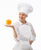 Beautiful young female cook showing orange on a plate Stock Photography