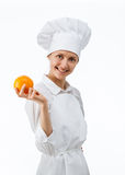 Beautiful young female cook showing an orange Stock Images