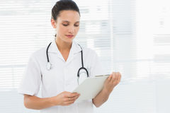 Beautiful young female doctor with clipboard Royalty Free Stock Images