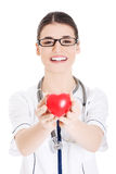 Beautiful young female doctor holding a heart. Royalty Free Stock Photo
