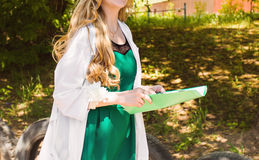 Beautiful young female doctor in medical gown holding a medical records. nurse with  medical records Royalty Free Stock Photography