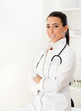 Beautiful young female doctor smiling with arms crossed Royalty Free Stock Photo