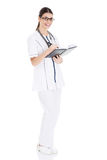 Beautiful young female doctor writing in a workbook. Royalty Free Stock Photo