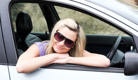 Beautiful young female driver wearing sunglasses Royalty Free Stock Photo